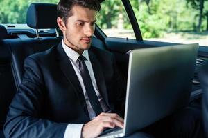 zakenman die laptop in auto met behulp van foto