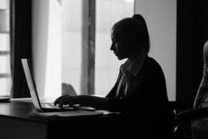 zakenvrouw typen op laptop achter haar bureau foto