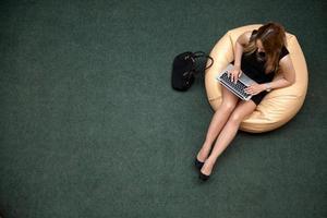 jonge vrouw die op laptop, bovenaanzicht werkt foto