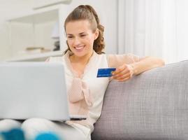 gelukkige huisvrouw met laptop en creditcard in de woonkamer foto