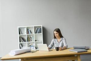 jonge vrouw die werkt in het kantoor foto