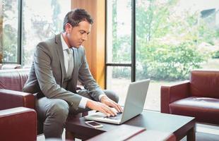 vrolijke knappe zakenman die op laptop werkt foto