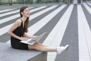 glimlachende vrouw die laptop in openlucht met behulp van foto