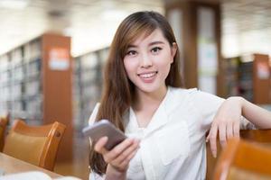 Aziatische mooie vrouwelijke student met behulp van laptop en mobiele telefoon