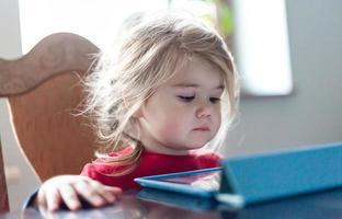 klein meisje met behulp van tablet foto