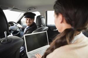 jonge zakenvrouw wordt chauffeur tijdens het werken foto