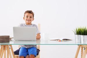 terug naar school. kleine jongen met behulp van zijn laptop foto