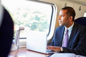 zakenman die aan trein aan het werk pendelt en laptop met behulp van foto