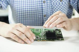 mannelijke handen die computerhardware herstellen