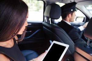 vrouw met behulp van tablet-computer in de taxi foto