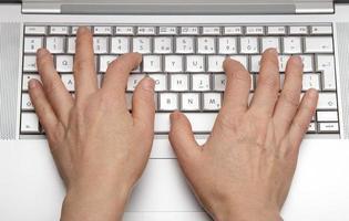 vrouwelijke handen afdrukken op het toetsenbord van een laptop foto