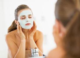 jonge vrouw gezichtsmasker toe te passen in de badkamer foto
