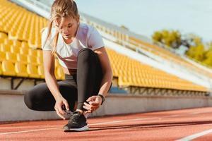 vrouw stropdas schoenveters in openlucht stadion foto
