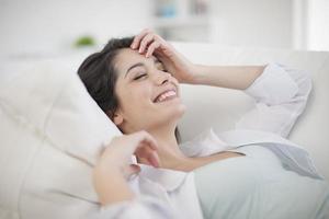 prachtige vrouw thuis ontspannen in de woonkamer foto