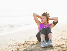 fitness jonge vrouw die buikkraken op strand doet foto
