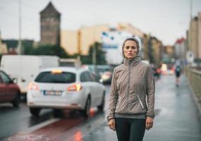 portret van fitness jonge vrouw in regenachtige stad foto