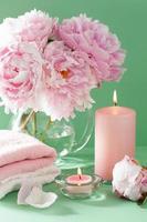 bad en spa met pioenroos bloemen kaarsen handdoeken foto