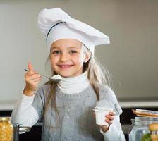 klein meisje proeven van verse yoghurt in de keuken en glimlachen foto