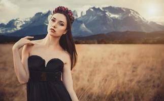 mooi meisje in een zwarte jurk met bloemen in de buurt van bergen foto