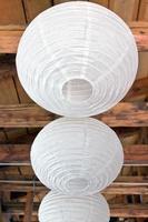 drie witte papieren lantaarns (lampoons) op houten plafond foto