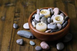 samenstelling met spa stenen, kaarsen op houten achtergrond foto