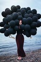mooi meisje dat met zwarte ballons loopt foto