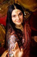 schoonheid zoete echte Indiase meisje in sari lachend op zwart foto