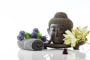 Boeddha hoofd op een witte achtergrond, handdoek, stenen en lotus