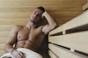 aantrekkelijke jonge man in sauna foto