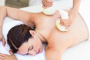 brunette die massage met kruidenkompressen heeft foto