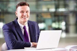 jonge blanke zakenman met behulp van laptopcomputer op het werk foto
