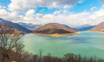 Kaukasische bergen in de buurt van het groene meer en verbazingwekkende wolken foto