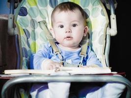 kleine blanke babyjongen zitten in chear met Kladblok foto