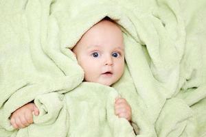 Kaukasisch jongetje bedekt met groene handdoek glimlacht vreugdevol foto