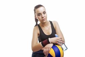 uitgeput Kaukasische vrouwelijke volleybal atleet zitten met fles water foto