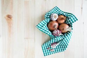 samenstelling van uien en knoflook in mand op houten tafel foto