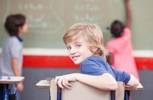 multi-etnische elementaire klas. kind camera kijken terwijl c