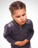 ziek klein meisje meisje pijn in de buik, buikpijn foto