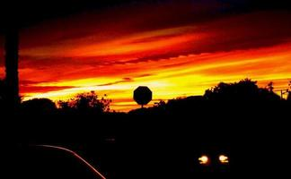 zonsondergang met stopbord afsteekt tegen vuur rode hemel foto
