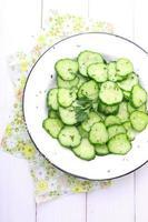 komkommersalade met dille en olie op een witte plaat foto