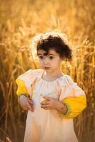 kind meisje in een veld van tarwe foto