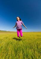 gelukkig meisje dat op een weide springt foto