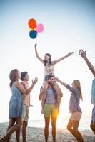 gelukkige vrienden dansen op het zand met ballon foto