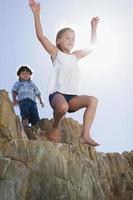 meisje buiten springen boulder foto