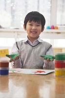 portret van lachende schooljongen vinger schilderen in de kunst klas, Peking foto