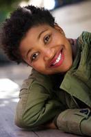 lachende jonge vrouw buiten zitten