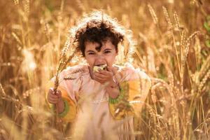 kind in een veld van tarwe foto