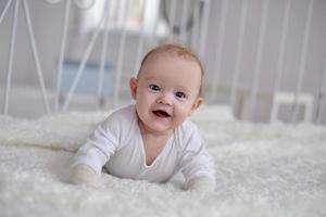 portret van een kruipende baby op het tapijt in de kamer foto