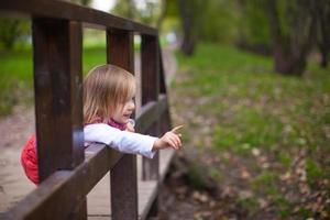 klein meisje buiten lopen, plezier maken en lachen foto