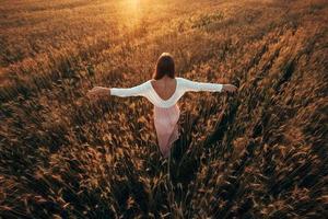 mooie brunette dame in een tarweveld bij zonsondergang foto